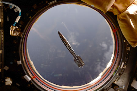 Mini Hugo rocket floating in front of an ISS window with the Earth in the background.